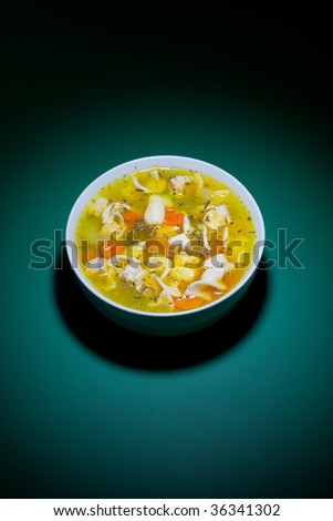 Fresh and hot bowl of soup on green table - stock photo
