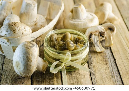 fresh and pickled champignons closeup on wooden surface