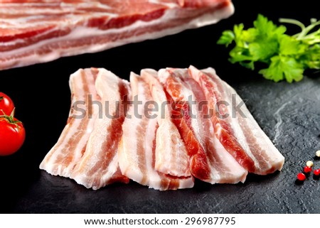 Fresh and raw meat. Steaks in a row ready to cook.  Raw pork. Fresh pork chop bacon and bacon and grilled BBQ. Background black blackboard.  - stock photo