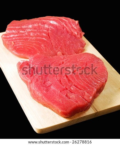 Fresh and raw tuna steaks isolated on a black background. - stock photo