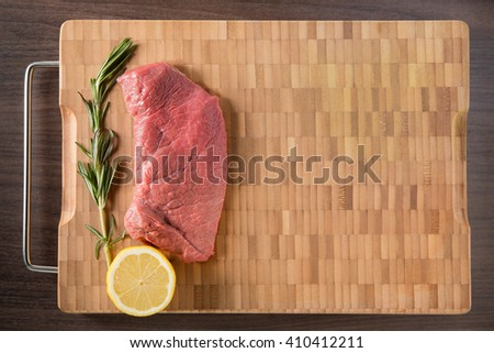 Fresh and raw veal meat. Steaks with seasonings in a row ready to cook. Bamboo and wooden board background with free text space. overhead view - stock photo