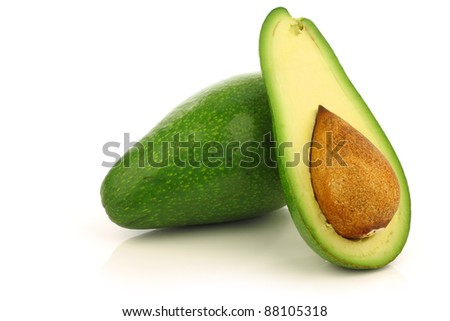 fresh and ripe avocado and a cut one on a white background - stock photo