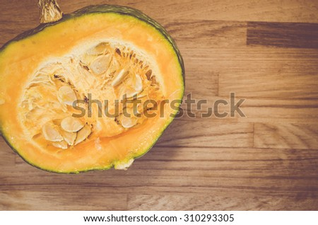 fresh and ripe half cut pumpkin on a natural wood background - organic vegetables