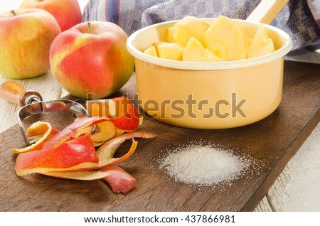 fresh and sliced apple pieces and sugar on wooden board to make apple compote - stock photo