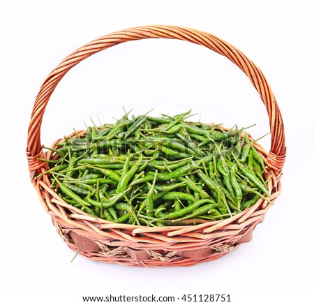 Fresh and spicy green chili peppers in rattan basket on white background - stock photo