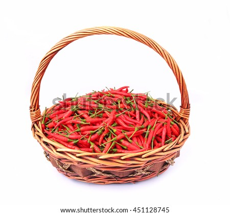 Fresh and spicy red chili peppers in rattan basket on white background - stock photo