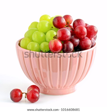 Fresh and sweet red and green grapes in pretty pink bowl on white background in horizontal format