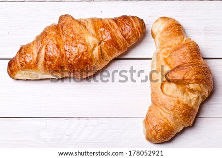 Fresh and tasty croissant on wooden table