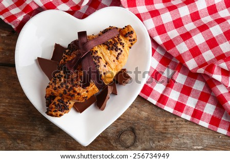 Fresh and tasty croissant with chocolate on plate, on wooden background - stock photo