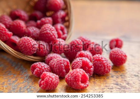 Fresh and tasty looking raspberries on a wooden table - stock photo