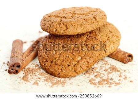Fresh and tasty oat cookies with cinnamon sticks on white background - stock photo