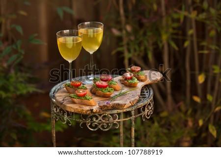 Fresh and tasty pesto bruschetta with wine - stock photo