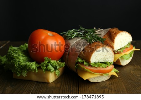 Fresh and tasty sandwich on wooden table on black background - stock photo