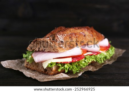 Fresh and tasty sandwich with ham and vegetables on paper on wooden background - stock photo