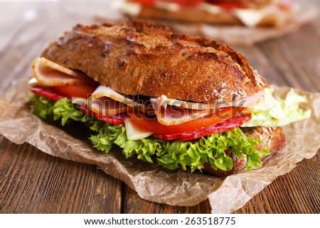 Fresh and tasty sandwiches with ham and vegetables on wooden background - stock photo