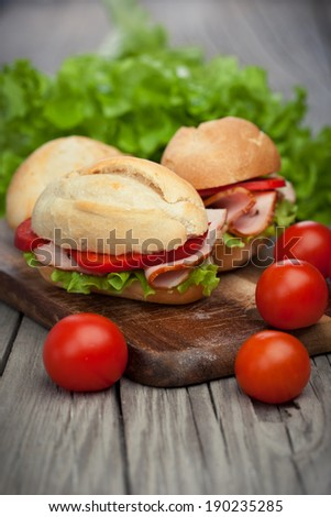 Fresh and tasty sandwiches  with ham, tomatoes and fresh green lettuce on wooden background - stock photo