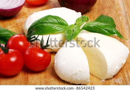 Fresh and tasty tomatoes, basil and mozzarella on wooden board - stock photo
