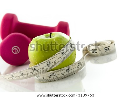 Fresh appetizing apple and brightly colored dumbbells tied with a measuring tape. Slight reflection, white background, focus on the apple