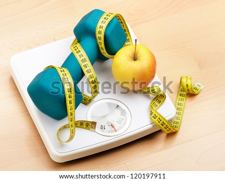 Fresh apple and dumbbells tied with a measuring tape on a weighting scale - stock photo