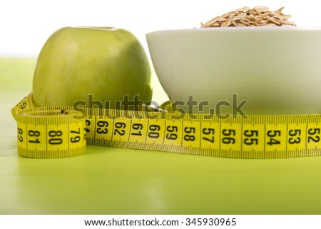fresh apple and oatmeal, centimeter on a green background