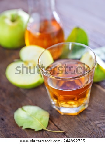 fresh apple juice in the glass and on a table - stock photo