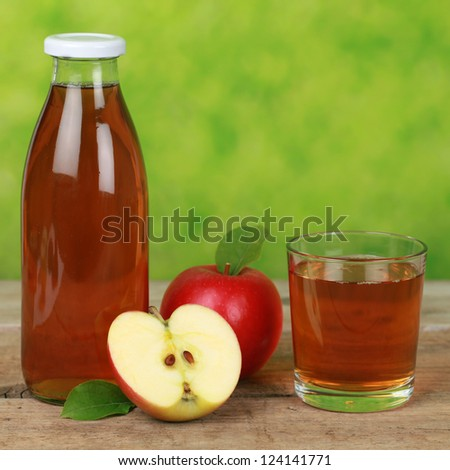 Fresh apple juice served in a bottle and in a glass - stock photo