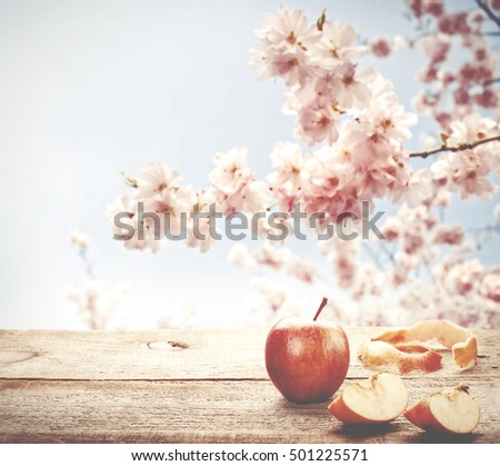 Fresh apple on wooden table with blue sky and blossom tree on background.