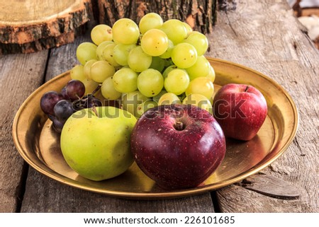 Fresh apples and grapes on golden plate over wooden background in domesic atmosphere - stock photo