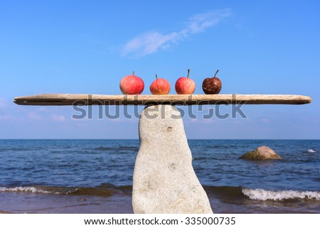 Fresh apples and rotten in balance on narrow plank - stock photo
