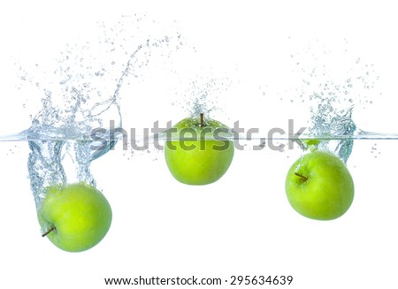 Fresh apples falling into water with splashes - stock photo