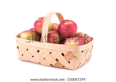 Fresh apples in a wooden basket, on white background
