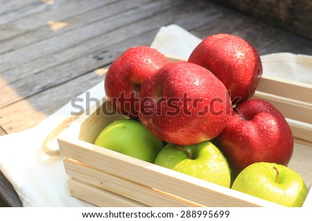 Fresh Apples in a wooden crate on wooden table background