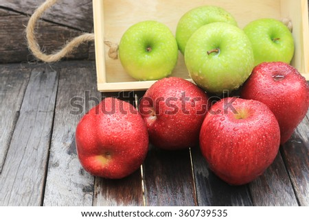 Fresh Apples in a wooden crate on wooden table background - stock photo