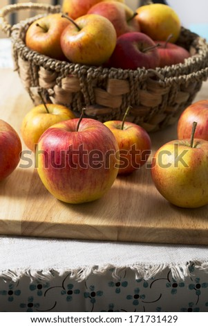 Fresh apples in basket and on board on top of table.