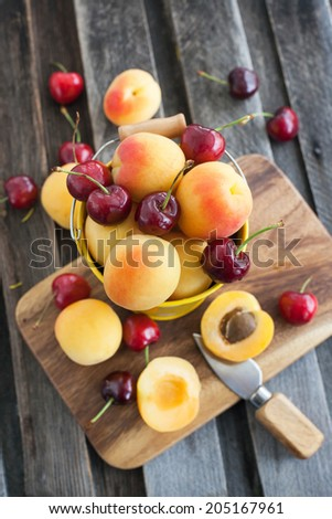 Fresh apricot and cherry in a yellow bucket - stock photo