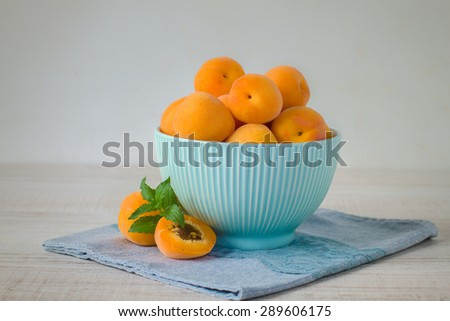 Fresh  apricot in blue bowl on  wooden table - stock photo