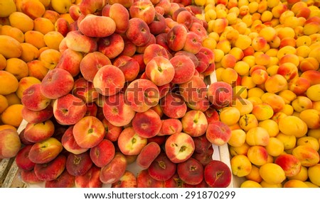 Fresh apricots and peaches on a street market stall - stock photo