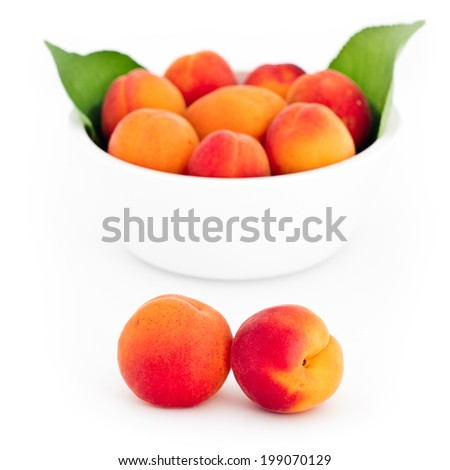 Fresh apricots in front and in the white bowl isolated on white background - stock photo