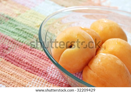 Fresh apricots in glass dish with pastel placemat as background.  Sunlit macro with extremely shallow dof. - stock photo