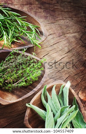Fresh aromatic herbs on old wooden background. Rosemary, thyme and sage - stock photo