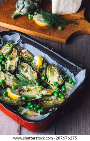 Fresh artichokes with parsley and young beans in a baking pan, parmesan in background. - stock photo