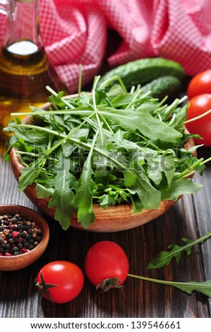 Fresh arugula leaves in wooden bowl with tomatoes, cucumber and olive oil on a wooden background