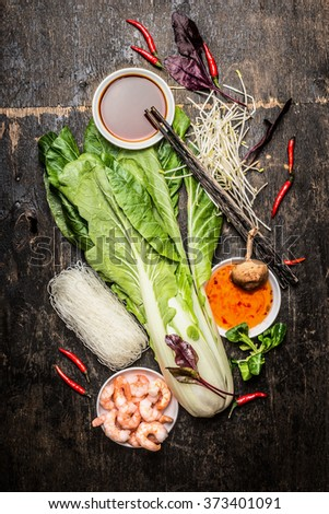 Fresh asian cooking ingredients with rice noodles and shrimps. Asian food vegetables and sauces. - stock photo
