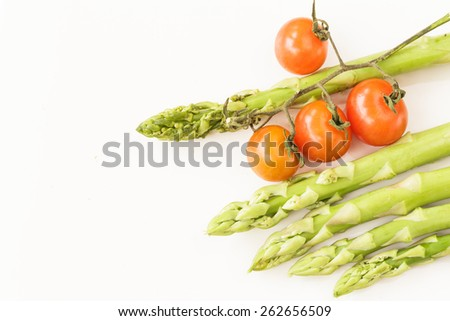 Fresh asparagus and tomatoes on white background. Vegetable food. - stock photo