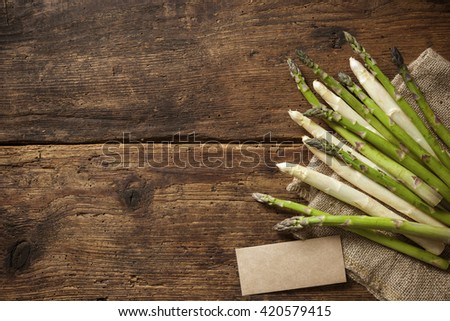 Fresh asparagus on wooden background with empty tag overhead shoot - stock photo