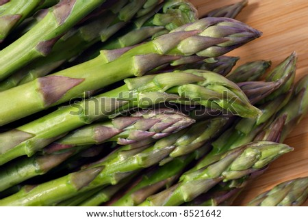 Fresh asparagus on wooden cutting board.  Macro with shallow dof - stock photo