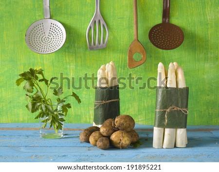 fresh asparagus, potatoes, parsley and vintage kitchen utensils - stock photo