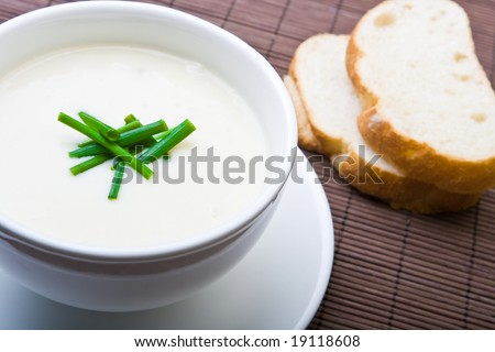 Fresh asparagus soup with bread and chives - stock photo