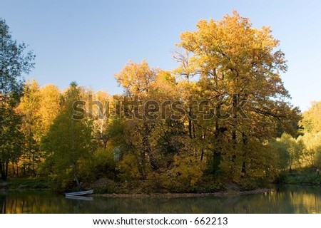 Fresh autumn forest on lake. Boat