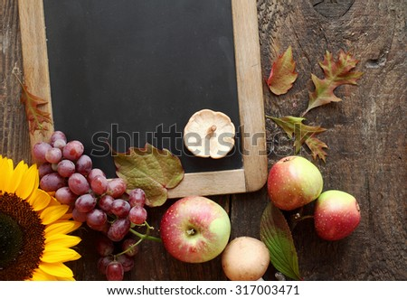 Fresh autumn fruit and sunflower arranged around a blank vintage slate with copyspace for your menu or recipe with grapes, apples and mushroom on a rustic wooden counter - stock photo